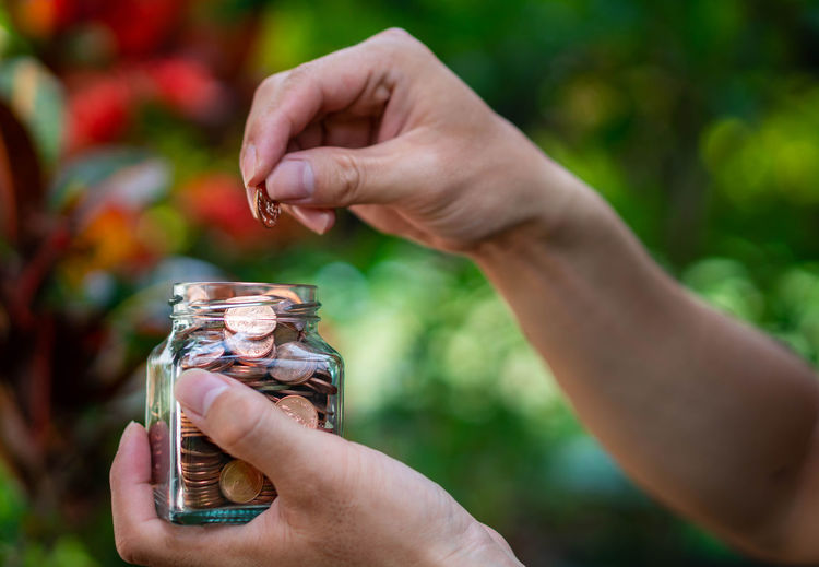 Close-up of hand holding jar against blurred background