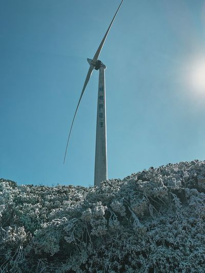 Low angle view of windmill on rock against sky