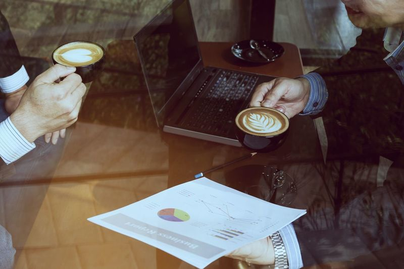 Midsection of businessman with coffee analyzing chart on office desk
