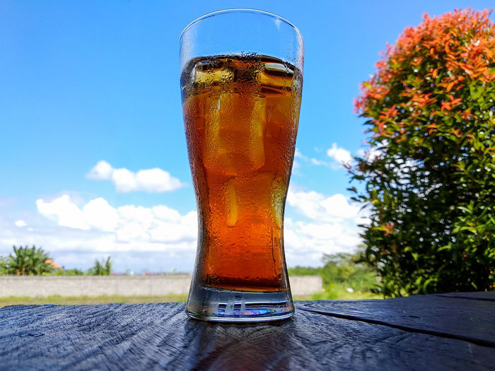 Close-up of beer glass on table against sky