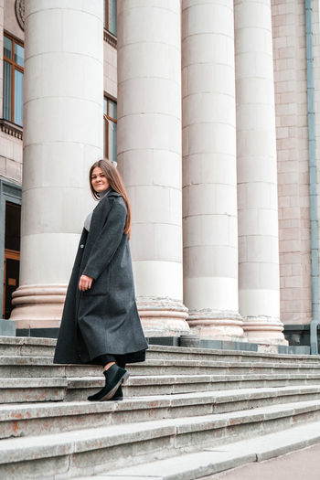 Young brunette woman walking up on stairs. long beautiful hair and long coat in business downtown.
