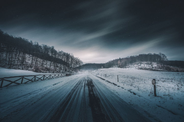 Snow covered road against sky at night