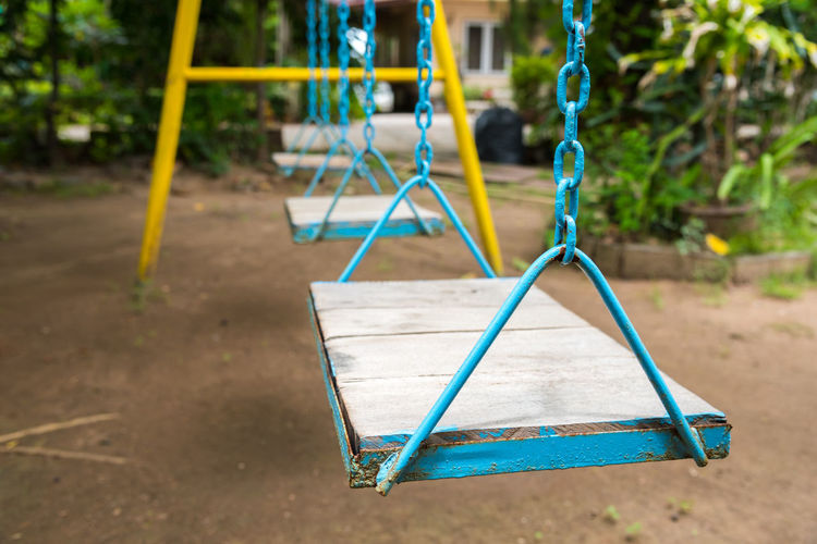 Empty swings hanging in park