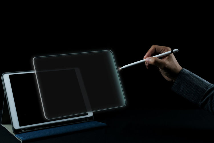 Low angle view of person using smart phone against black background