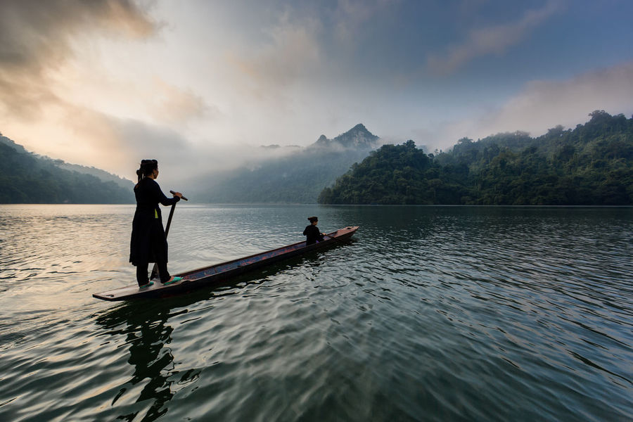 Early morning on Ba Be lake, mother and daughter cross the lake on traditional pirogue Beauty In Nature Cloud - Sky Lake Lifestyles Mountain Nature Nautical Vessel Outdoors People Real People Rowing Scenics Sky Two People Water
