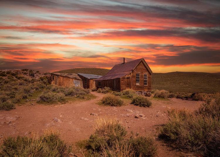 House on field against orange sky