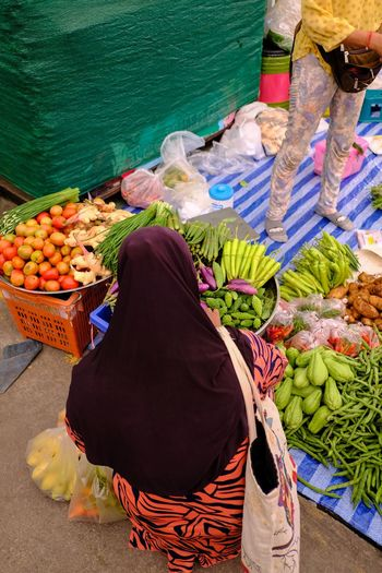 High angle view of woman buying vegetables