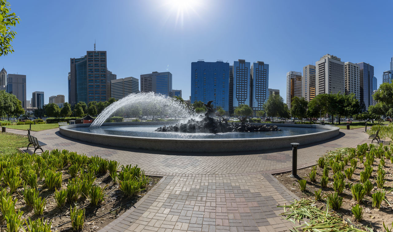 FOUNTAIN IN PARK BY BUILDINGS AGAINST SKY