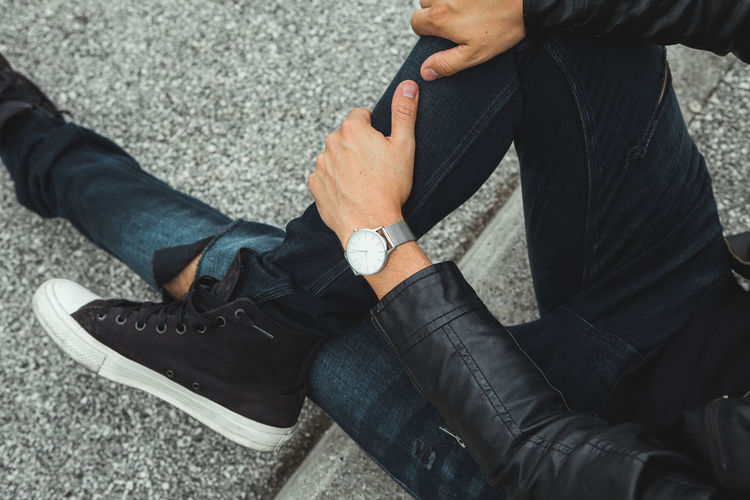 Young Man casually dressed wearing analog watch in the Urban environment Men Real People Casual Clothing Human Body Part Low Section Lifestyles Two People People Body Part Day High Angle View Sitting Human Leg Hand Human Hand Midsection Time Shoe Outdoors Jeans Leather Watch Wrist Watch Jewellery Jewelry Young Adult Young Men City City Life Urban Street