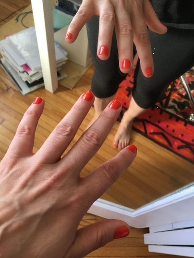 Cropped image of woman hand with red nail polish standing against mirror