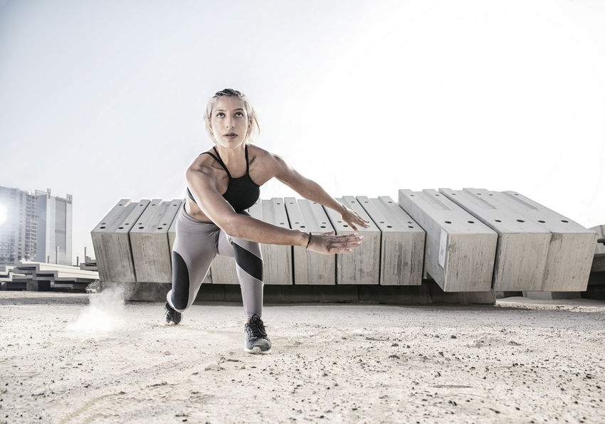 Middle Eastern Girl with short braided hair exercising on a dusty construction site wearing gray and black fitness outfit on a hot bright sunny day. Exercising Jumping Off Rocks Sitting Adult Architecture Beautiful Woman Bright Day Built Structure Day Dusty Fitness Model Front View Full Length Hot Day ☀ Leisure Activity Lifestyles Looking At Camera Middle Eastern Woman One Person Portrait Real People Sky Sports Clothing Standing Stretching Women Wood - Material Young Adult Young Women