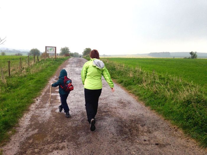 Mother and son walking on footpath against sky
