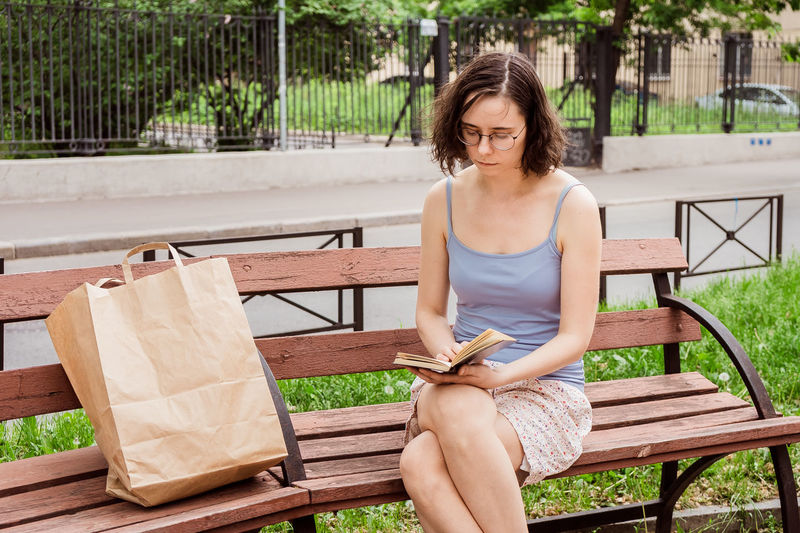 A girl reads a book on a bench in the city. interesting and useful leisure time alone