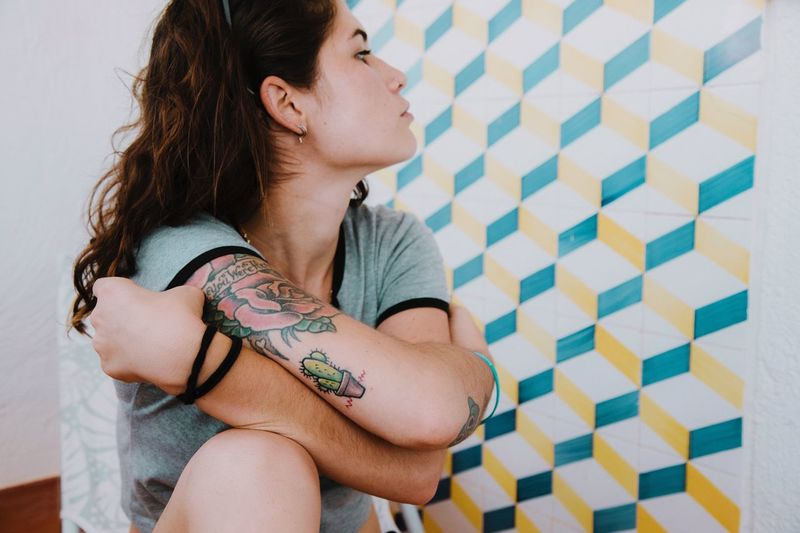 Young woman showing off her tattoo on arm while looking away at home