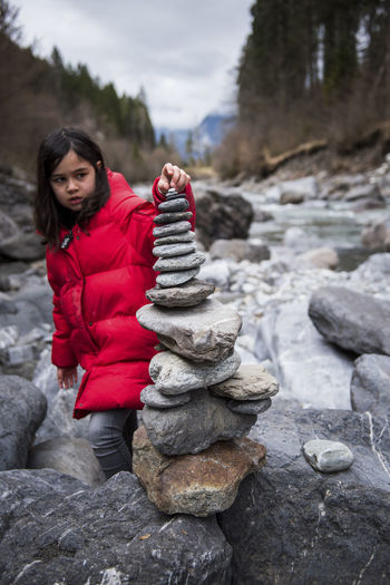 Hiking Clothing Cold Temperature Day Focus On Foreground Full Length Hikingadventures Leisure Activity Lifestyles Nature One Person Outdoors Real People River Rock Rock - Object Solid Stone - Object Warm Clothing Winter Women Young Adult Young Women