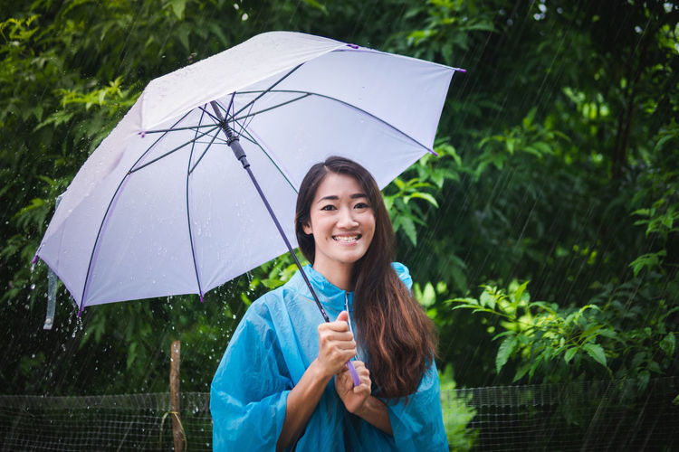 Portrait of smiling woman standing on wet rainy day