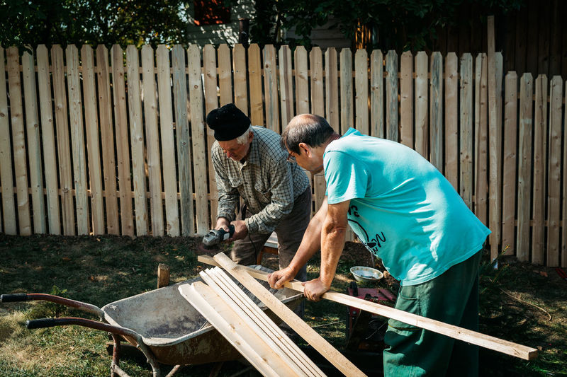 Working together Men Real People Two People Wood - Material Day Front Or Back Yard Casual Clothing Bending Boundary Fence Teamwork Adult Standing Males  Togetherness Outdoors Nature Wheelbarrow Carpenter Carpentry Yard Working Hard Hat Summer Old Men