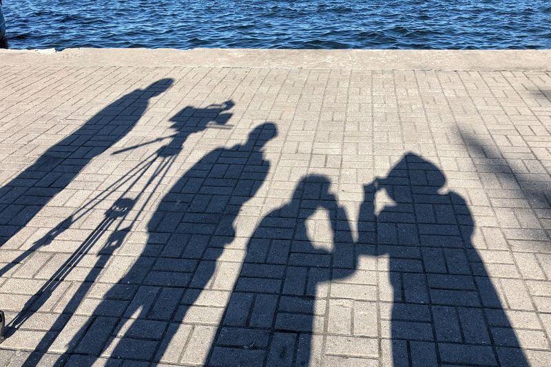 Shadow of people on footpath by sea