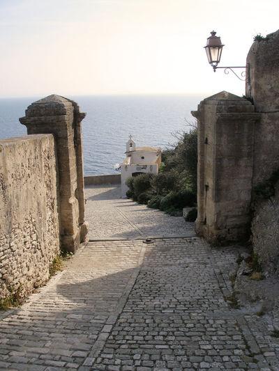 Walkway by sea against clear sky