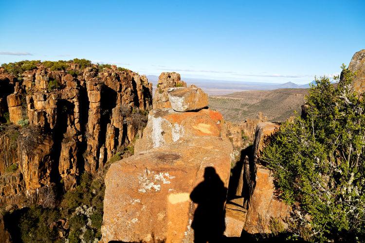 Rear view of women on rock against sky