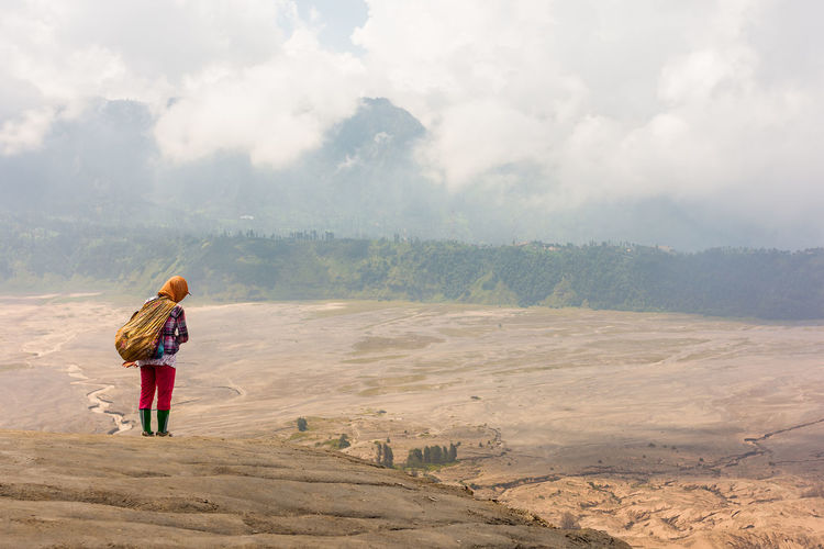 A local women stands on the outer edge of the crest of the active volcano mt Bromo looking down on the surround ash flats in East Java, Indonesia. INDONESIA Ash Flats Beauty In Nature Casual Clothing Cloud - Sky Day Environment Full Length Land Landscape Leisure Activity Lifestyles Local Woman Mountain Mt Bromo Nature Non-urban Scene One Person Outdoors Real People Scenics - Nature Sky Standing Tranquil Scene Volcano