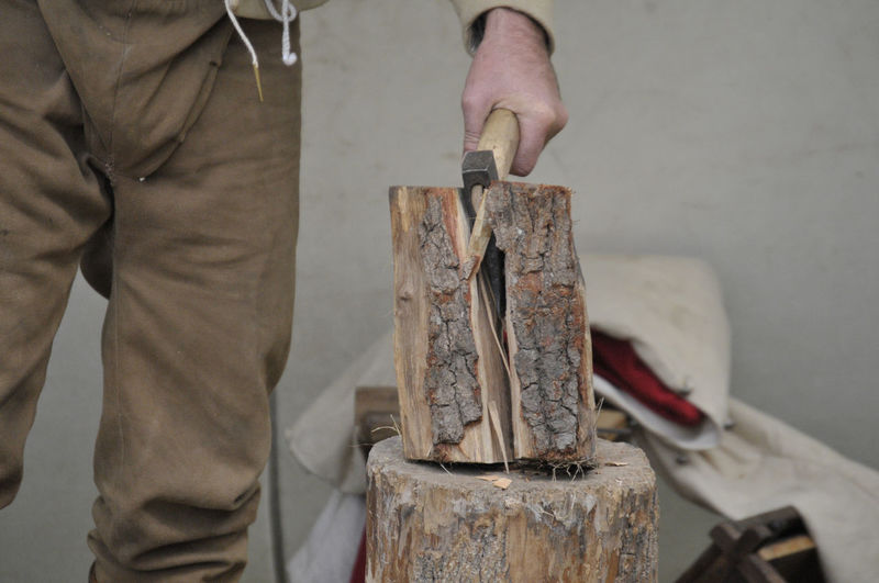Midsection of man chopping wood