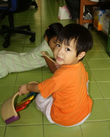 Portrait of boy holding musical instrument by sister on tiled floor at home