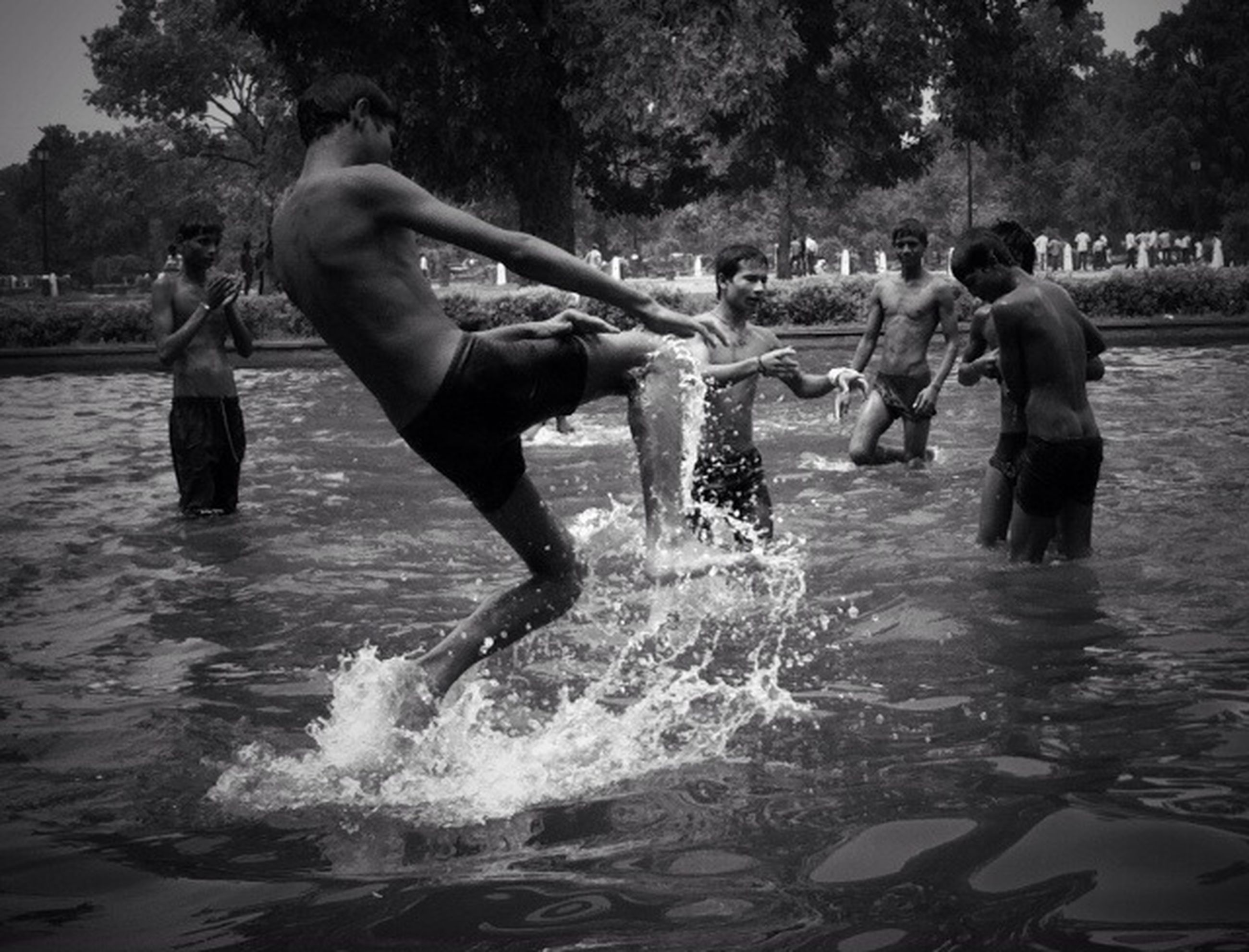 water, lifestyles, men, leisure activity, motion, enjoyment, tree, splashing, fun, full length, person, playing, large group of people, boys, togetherness, fountain, outdoors, jumping, day