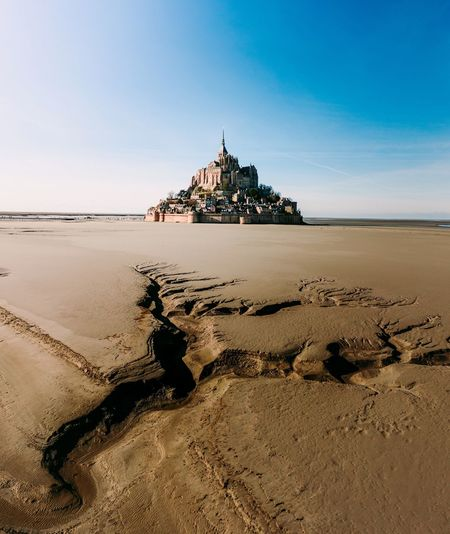 St michel Lemontsaintmichel Sky Land Beach Sand Nature Built Structure Water Clear Sky Architecture Sunlight Spirituality Scenics - Nature No People Religion Beauty In Nature Building Exterior Sea Horizon Over Water Day Travel Destinations