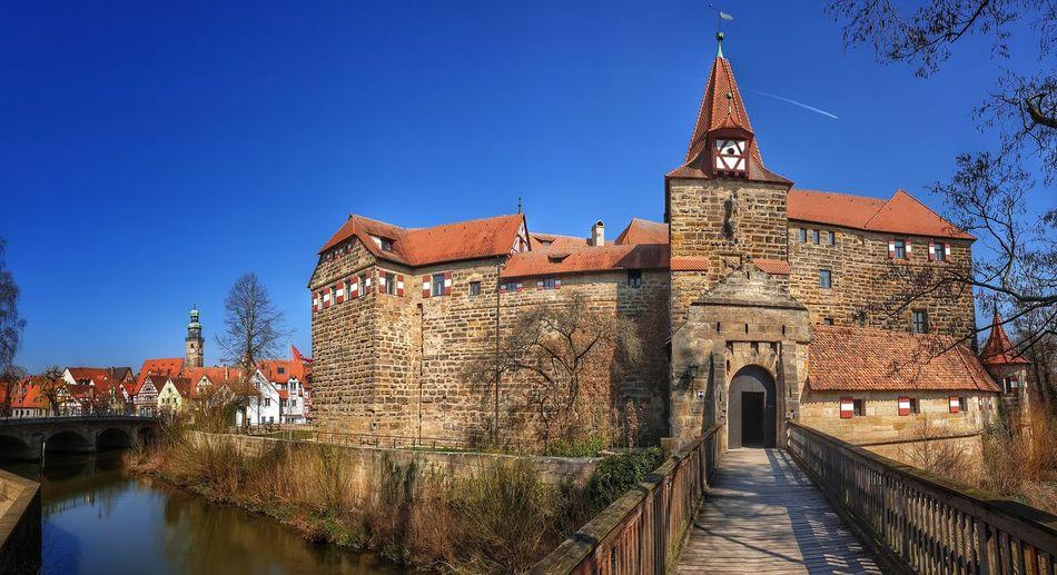 Canal amidst buildings against blue sky