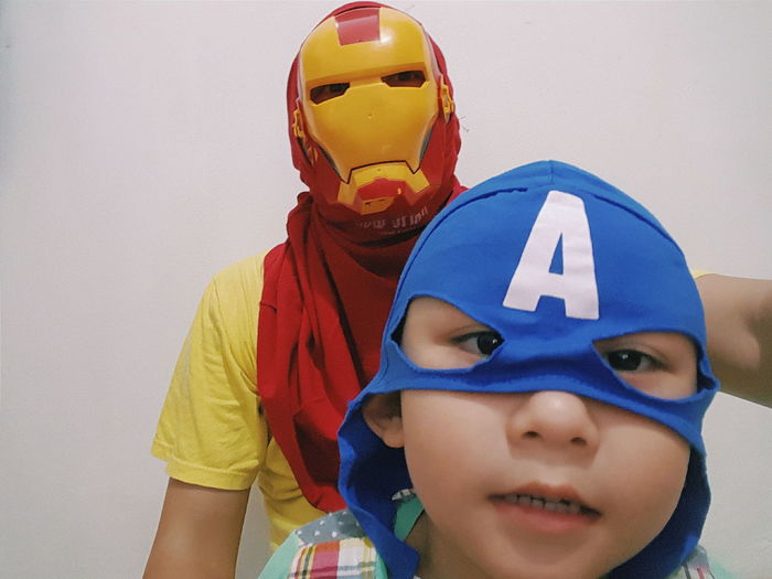 Captain America Childhood Content Cosplay Creativity Cute Elementary Age Facial Expression Fatherhood Moments Focus On Foreground Front View Green Color Headshot Human Face Innocence Ironman Kids Playing Leisure Activity Lifestyles Looking At Camera Making A Face Mask - Disguise Person Roleplay Sibling