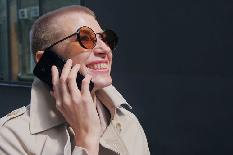 Smiling businesswoman talking on phone while standing against wall