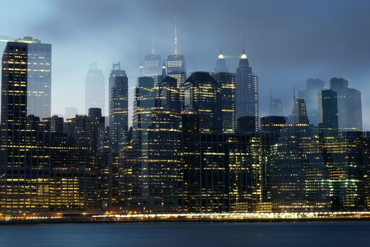 Digital composite image of illuminated cityscape against sky at dusk
