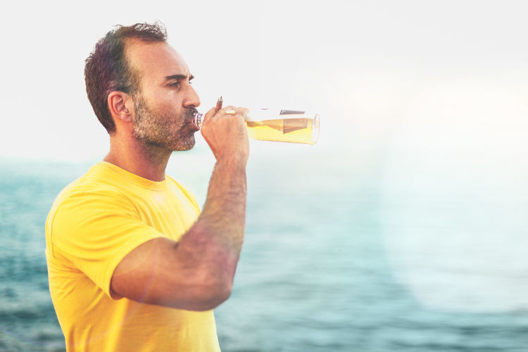 Mid aged man drinking beer on the seaside Man Drinking Glass Beauty In Nature Water One Person Drinking Drink Sea Refreshment Facial Hair Men Bottle Beard Holding Beer - Alcohol Casual Clothing Food And Drink Beer Alcohol Nature Lifestyles Standing Glass Outdoors Seaside Copy Space Copy Space In The Sky Yellow T Shirt Mid Aged Woman Adult Fourty Room For Text Looking Away Looking Away From Camera Teal Orange Color Color Filtered Image Harbor Portrait Coast Mediterranean