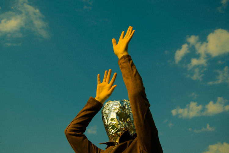 Low angle view of woman with covered face standing against sky