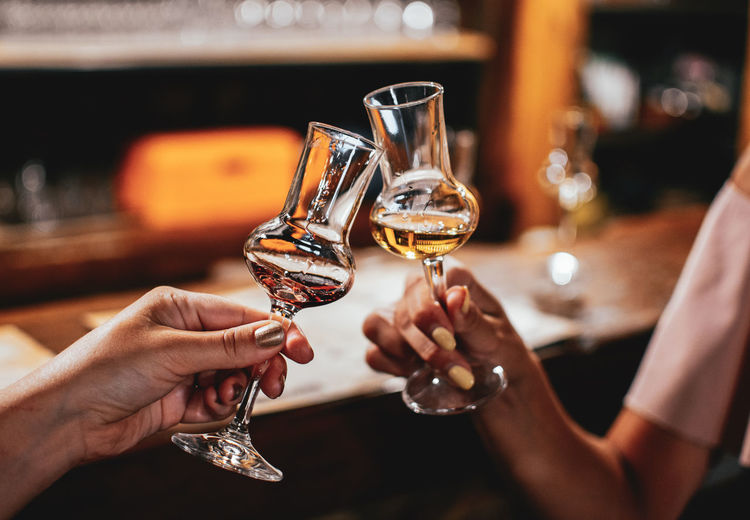 Hands holding brandy glasses in bar. night out, friends, women, lifestyle.