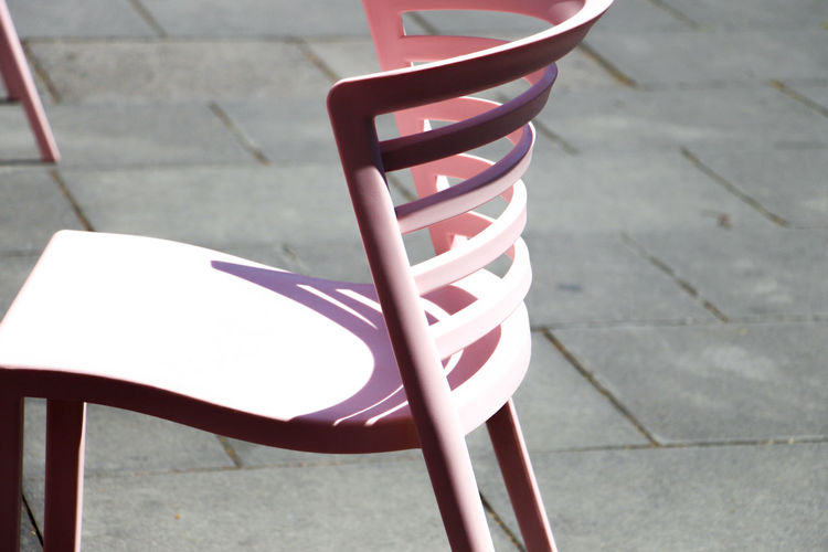 Chair Seat Day Absence Empty No People High Angle View Focus On Foreground Red Sunlight Footpath Outdoors Street Shadow Relaxation Metal Striped White Color Still Life City Paving Stone Pink Chair Architecture Urban Streetphotography Artistic Photography Arts Culture And Entertainment Art And Craft Shadows & Lights Schattenspiel  Straßenkunst Straßenfotografie