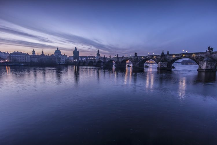 Charles bridge over river in city against sky at dusk