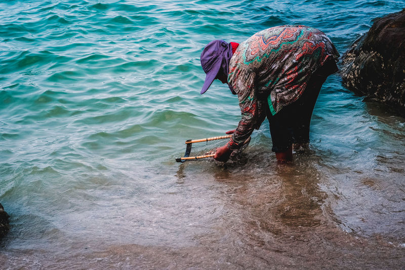 Rear view of woman fishing in sea