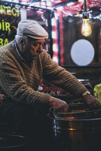 Man holding food at market stall at night
