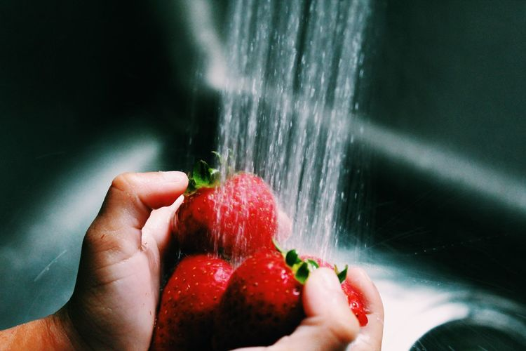 Cropped hands washing strawberries