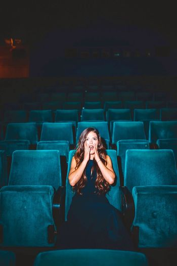 Shocked young woman looking away while sitting on seat in theater
