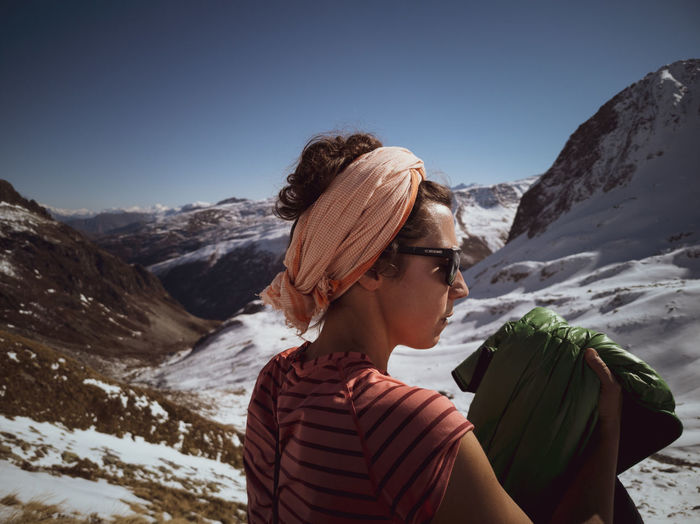 Rear view of woman on snowcapped mountain against sky