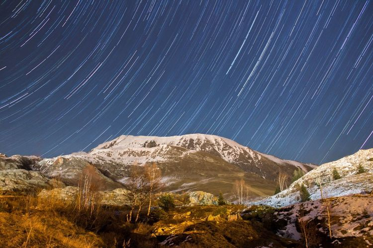 Scenic View Of Snow Covered Mountains Against Star Trails