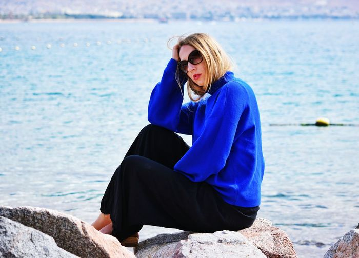 girl in blue sweater sitting at the red sea in eilat Blue Eilat Israel Red Sea Sea Seaside EyeEm Selects Only Women Sea One Woman Only One Person Adult Adults Only Mature Adult Sitting One Mature Woman Only Water People Eyeglasses  Women Beach Day Outdoors Full Length Nature Horizon Over Water Go Higher #FREIHEITBERLIN