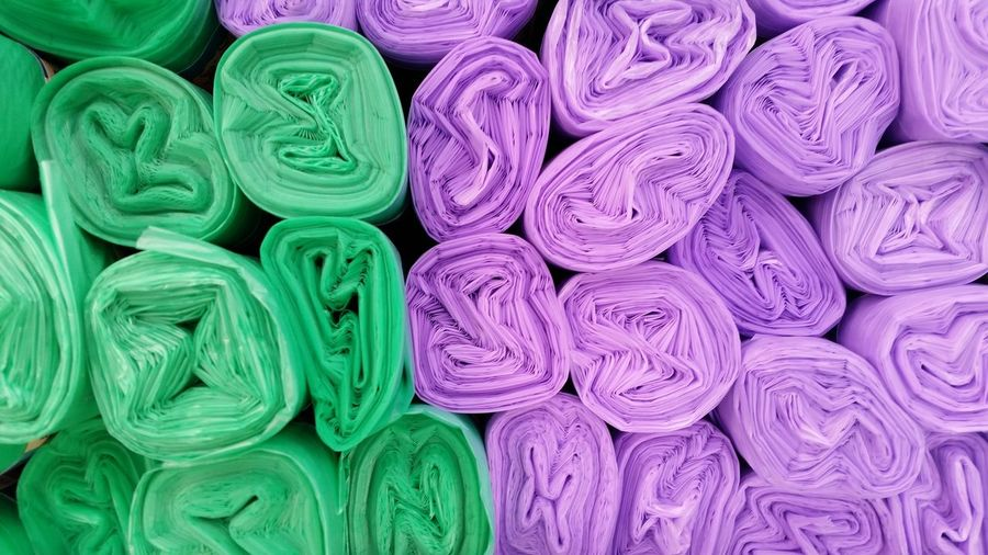 Full frame shot of purple and green garbage bags for sale at market stall