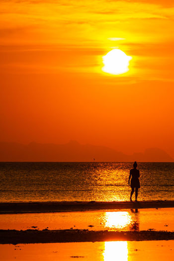 Silhouette people standing on beach against orange sky