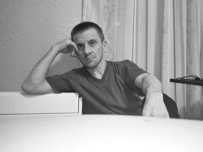 Portrait of man sitting on wall at home