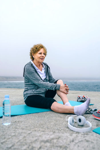 Senior sportswoman relaxing on yoga mat by sea pier Exercising Happiness Happy Headphones Modern Pier Vitality Woman Active Activity Caucasian Female Fitness Healthy Lifestyles Older  One Person Outdoors People Real People Sea Senior Sport Sportswear Vertical