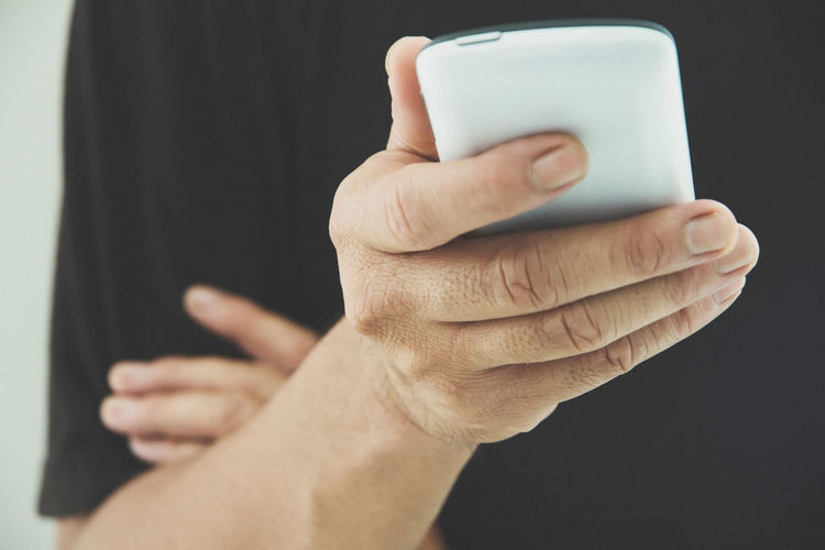 Midsection Of Man Using Phone